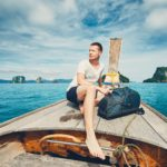 Young man (tourist) with backpack on the traditional long tail boat against islands between Phuket and Krabi in Thailand.