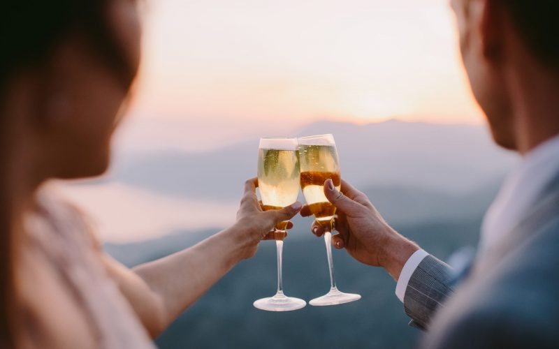 couple drink champagne at sunset. Honeymoon couple drink champagne at sunset together outdorrs with mountains view.
