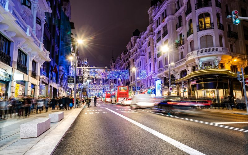 Madrid, Spain - December 15, 2018: Gran Via Avenue illuminated at Christmas with neon lights and traffic restrictions by the new mobility plan from City Hall called Madrid Central