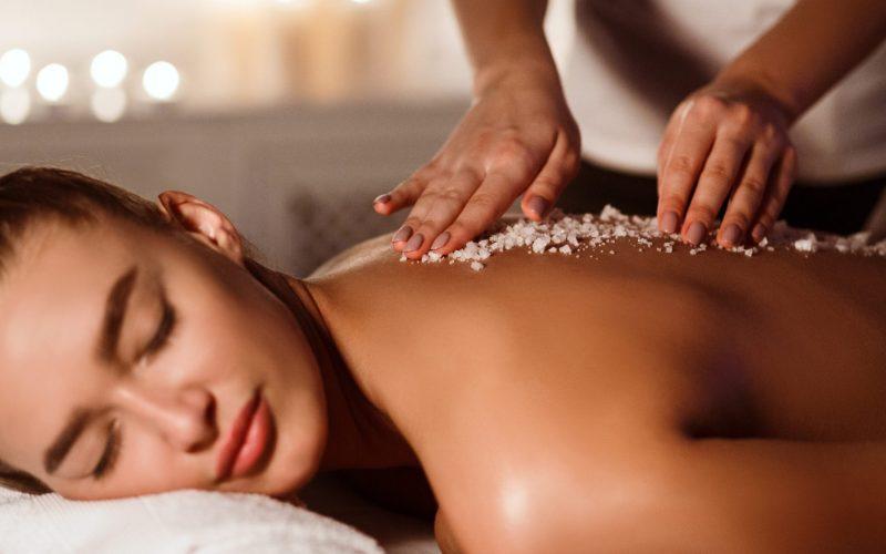 Woman enjoying salt scrub massage at spa salon, closeup